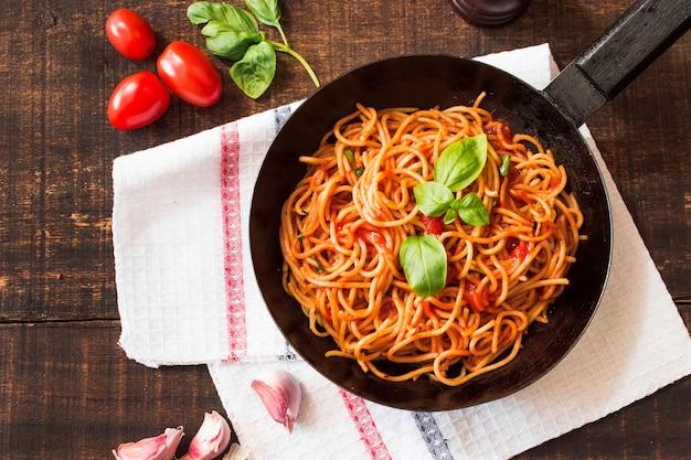 Espaguete com folhas de manjericão na frigideira na mesa de madeira com ingredientes