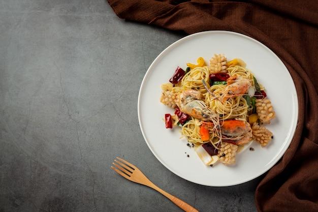 Espaguete com marisco misto picante em fundo escuro
