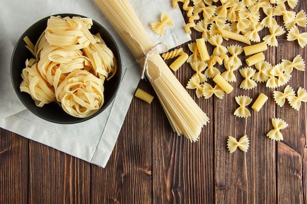 Espaguete com massa crua sortida em madeira e fundo de toalha de cozinha, configuração plana.