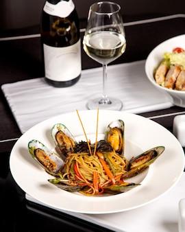 Espaguete com mexilhões e pimentões, servido com vinho branco