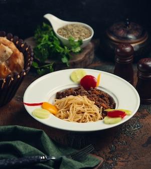 Espaguete com molho de carne e legumes.