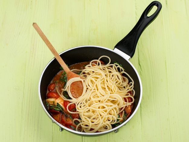 Espaguete com molho de tomate e ervas em uma panela