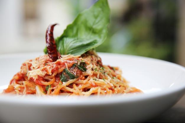 Espaguete com molho de tomate e manjericão fresco na madeira, massas italianas