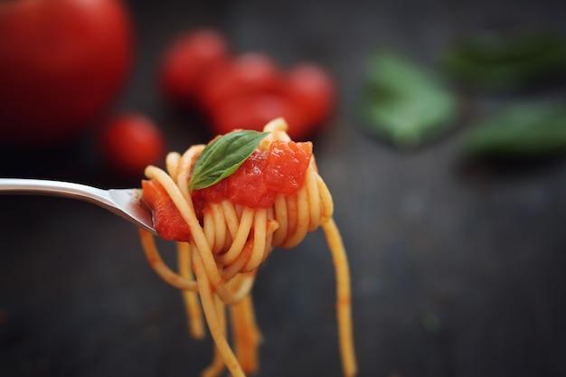 Espaguete com molho de tomate e manjericão no fundo escuro de madeira