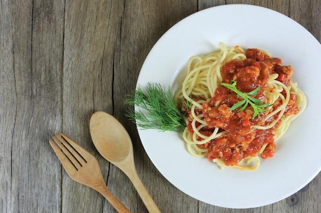 Espaguete com molho de tomate em um prato branco no fundo do assoalho de madeira