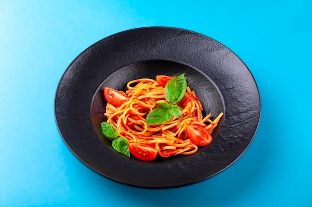 Espaguete com molho de tomate, folhas de manjericão, tomate cereja