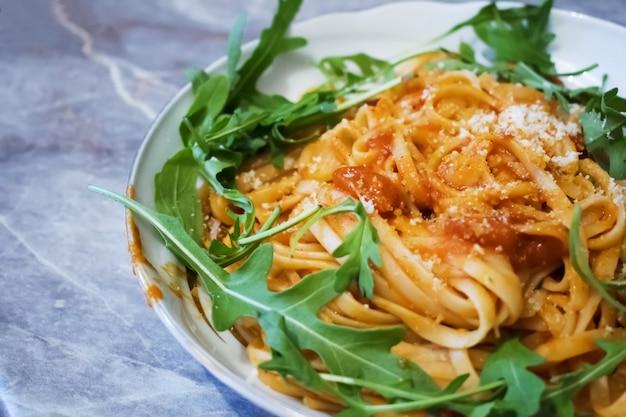 Espaguete com molho de tomate na mesa de madeira