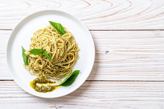 Espaguete com molho pesto, azeite e folhas de manjericão.