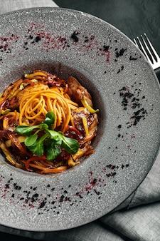 Espaguete com pato e legumes. cozinha italiana, bela porção de macarrão em um prato cinza e espaço escuro.