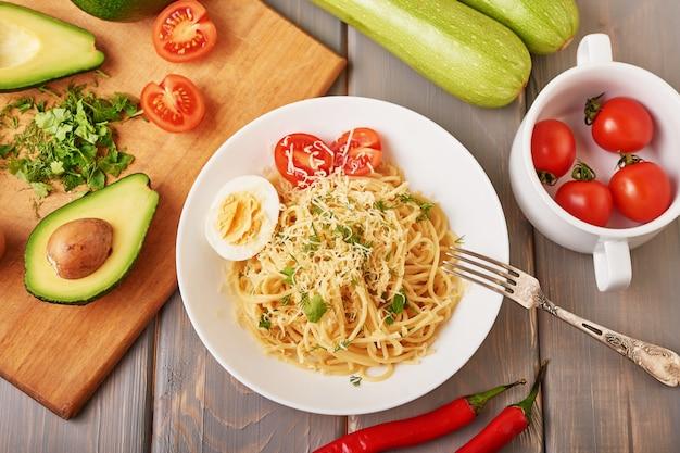 Espaguete com vegetais, abacate, pimentas doces, tomates de cereja e queijo parmesão como parte do prato.