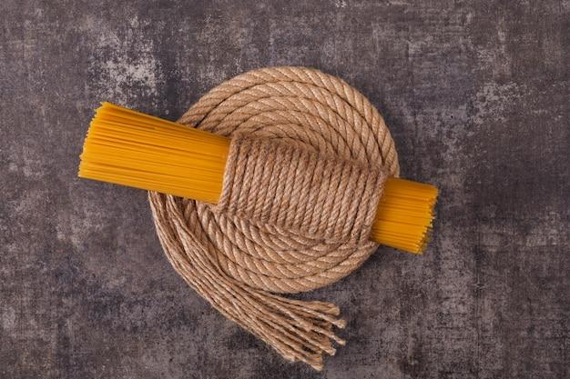 Espaguete cru amarrado com uma vista superior de corda na superfície escura