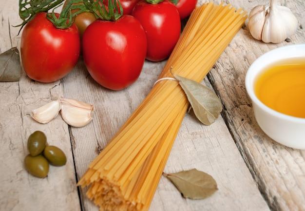 Espaguete cru ao lado de tomates vermelhos frescos em um ramo de alho, azeite e folhas de louro em uma superfície de madeira