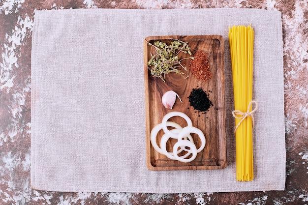 Espaguete cru com ervas frescas na mesa de madeira.