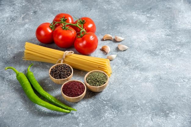 Espaguete cru com legumes em um fundo de mármore.