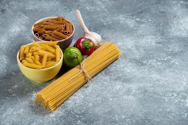 Espaguete cru com legumes na placa de madeira.
