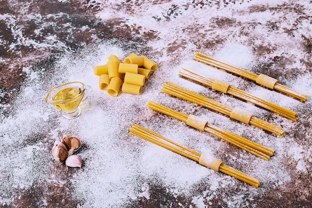 Espaguete cru cru e macarrão na mesa da cozinha de madeira.