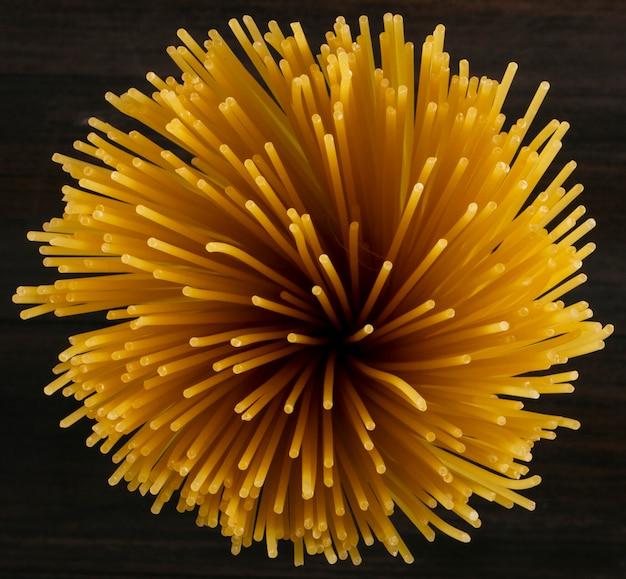 Espaguete cru de vista superior padrão em uma superfície de madeira