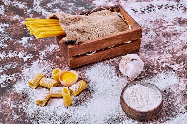 Espaguete cru e macarrão com farinha na mesa de madeira.