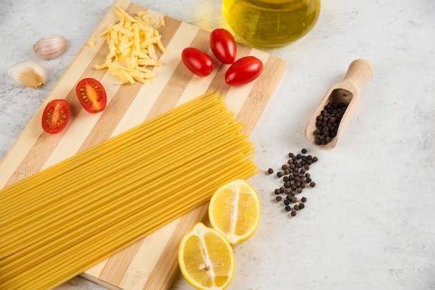 Espaguete cru, óleo e legumes frescos na placa de madeira.