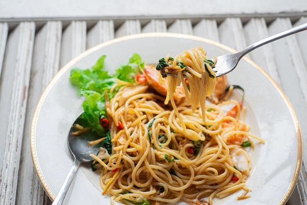 Espaguete de frutos do mar no garfo com pimentão e manjericão na madeira velha