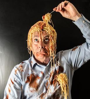 Espaguete de homem comendo com molho de tomate na cabeça
