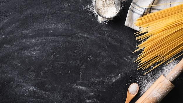 Espaguete de macarrão caseiro fazendo fundo em textura preta, espaço de cópia, vista superior, banner