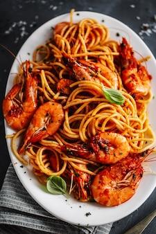 Espaguete de macarrão com camarão e molho de tomate servido no prato na superfície escura. fechar-se.