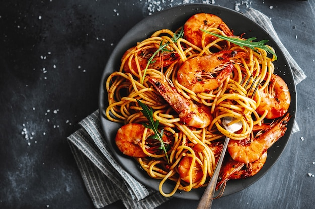 Espaguete de macarrão com camarão e molho de tomate servido no prato na superfície escura. vista do topo.