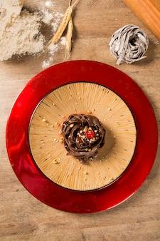 Espaguete de macarrão de chocolate cozido com molho de framboesa.