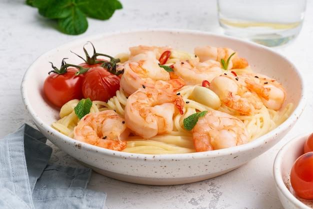 Espaguete de massa de frutos do mar com camarão frito, molho bechamel, folhas de hortelã e tomate na mesa branca