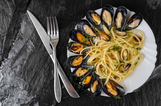 Espaguete de massa italiana com mexilhões e salsa. conceito de comida deliciosa.