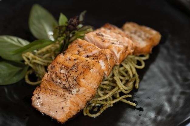 Espaguete de salmão em uma placa preta