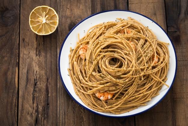 Espaguete de trigo integral com camarão na madeira