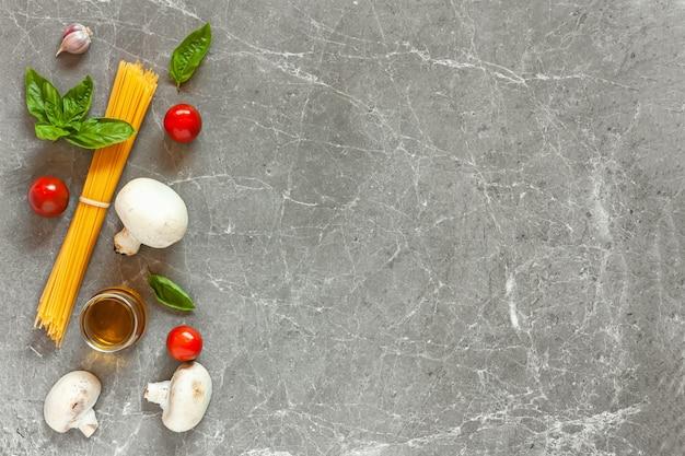 Espaguete e ingredientes em uma mesa de pedra