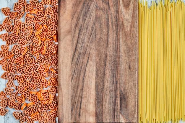 Espaguete e macarrão em forma de coração espalhados pela tábua de madeira.