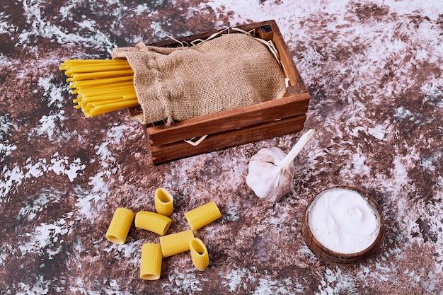 Espaguete e macarrão na mesa de madeira.