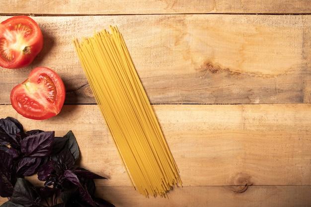 Espaguete e manjericão na mesa de madeira. ingredientes para massas