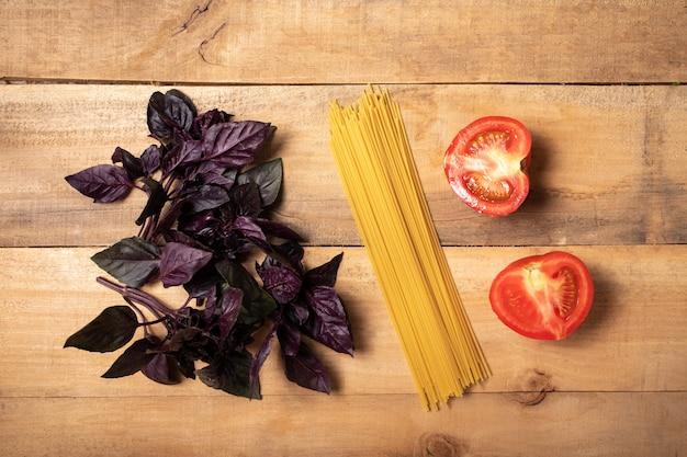Espaguete e manjericão na placa de madeira. ingredientes para massas