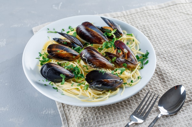 Espaguete e mexilhão com colher, garfo em um prato em gesso e toalha de cozinha