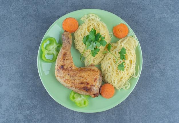 Espaguete e perna grelhada na placa verde.