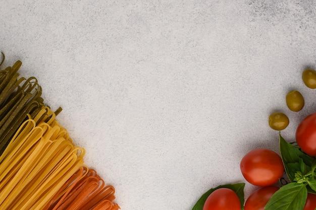 Espaguete e vegetais de cores diferentes em uma pedra de plano de fundo texturizado. macarrão verde com espinafre, macarrão vermelho com tomate e macarrão clássico em frente ao tomate cereja com capas de sapatos e azeitonas.