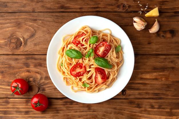 Espaguete em molho de tomate com queijo e manjericão em um espaço de madeira