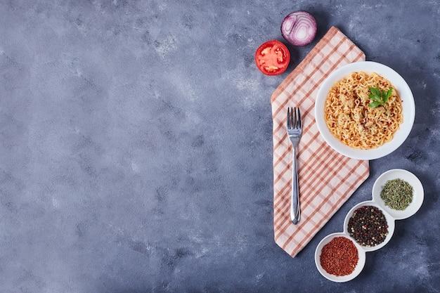 Espaguete em um prato branco com especiarias ao redor.
