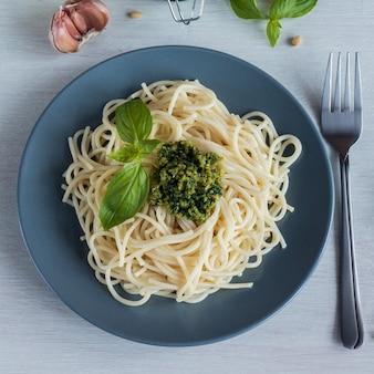 Espaguete. espaguete com molho pesto caseiro, azeite e folhas de manjericão. vista do topo