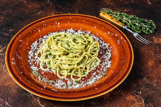 Espaguete espaguete macarrão com molho pesto e parmesão. fundo escuro. vista do topo.