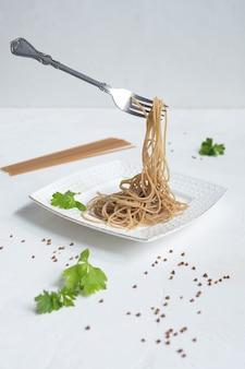 Espaguete feito de trigo sarraceno em uma mesa branca.