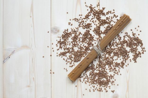 Espaguete feito de trigo sarraceno sobre uma mesa de madeira.