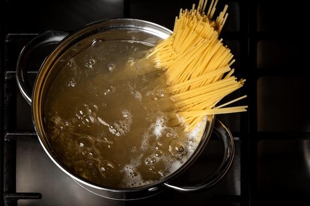 Espaguete fervendo na panela no fogão na cozinha.