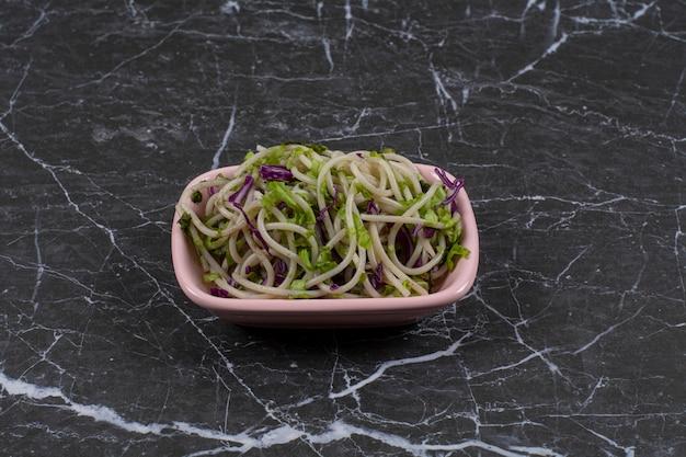 Espaguete fresco feito com molho de vegetais em uma tigela rosa.