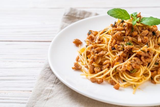 Espaguete frito com carne de porco picada e manjericão